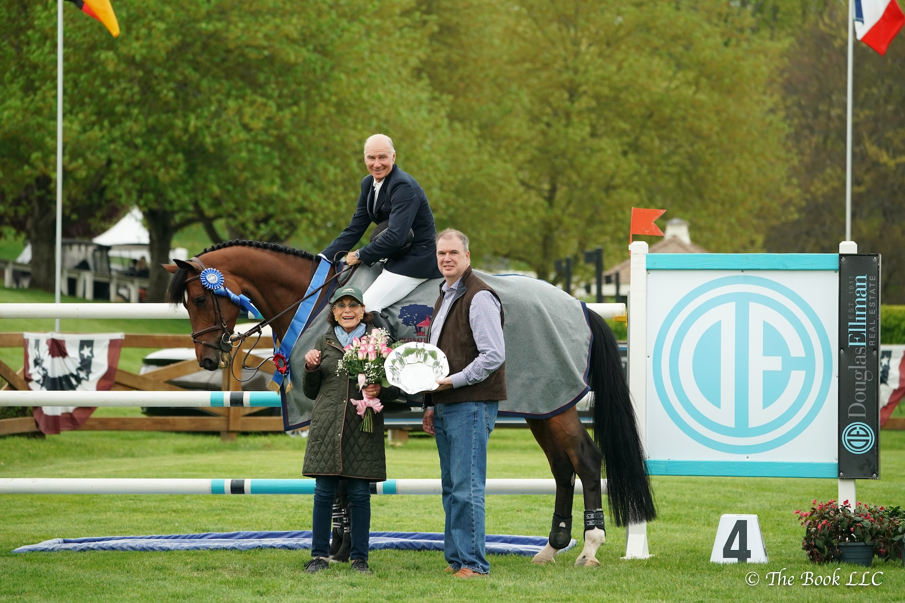 Mario Deslauriers (CAN) and Amsterdam 27 are joined by owner Rosalind Schaefer to be presented as winners of the $35,700 New York Welcome Stake CSI2*, presented by Douglas Elliman Real Estate, by Michael Fitzgibbon (center), Executive Manager of Sales at Douglas Elliman during the 2019 Old Salem Farm Spring Horse Shows at Old Salem Farm in North Salem, NY.<br><b>Photo by <a href='http://www.thebookllc.com/'target='_blank'>The Book</a></b>
